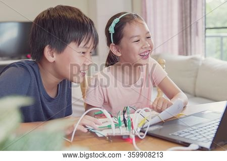 Mixed Race Young Asian Children Having Fun Learning Coding Together, Learning Remotely At Home, Stem