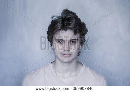 Portrait Of A Sympathetic Young Man On Gray Background, Toned