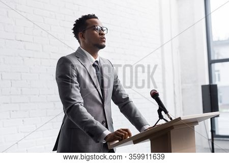Confident African American Business Speaker Standing On Podium With Microphone In Conference Hall