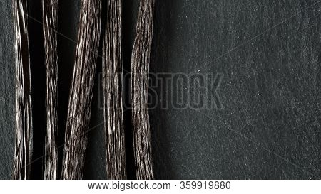 Closeup Detail On Five Vanilla Beans On Black Slate Board, View From Above, Empty Space For Text Rig