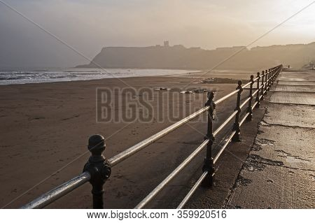 Coastal Headland With Castle And Metal Railings In The Morning Mist On The Sea Front