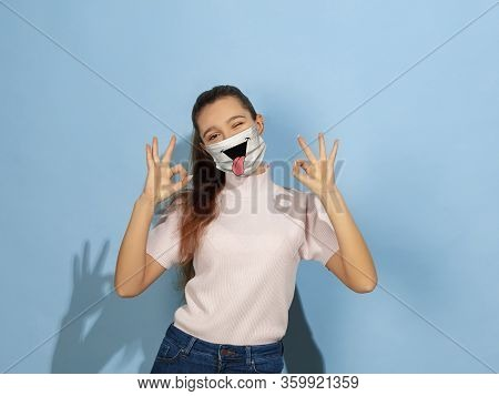 Nice Sign. Portrait Of Young Caucasian Girl With Emotion On Her Protective Face Mask Isolated On Stu