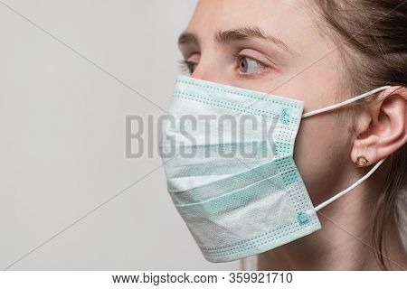 Young Woman Wearing Surgical Mask With Ear Rubber Straps. Portrait Close Up Side View.