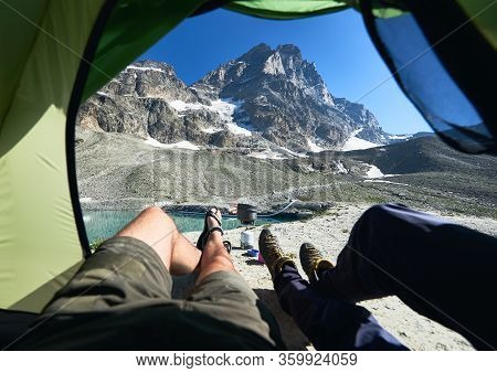 Male Legs Inside Camp Tent With Snowy Mountain On Background. Two Travelers Lying Inside Tourist Ten
