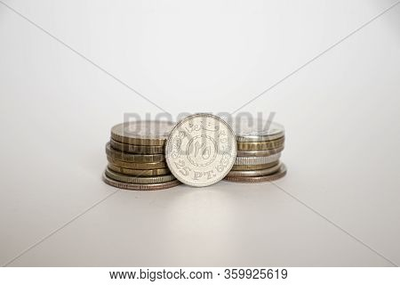 Twenty Five Piast Coin. A Coin On A White Background Stands Vertically Next To Other Coins Piled One