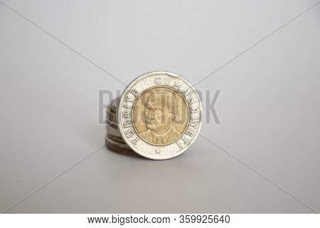 Turkish Lira Coin. A Coin On A White Background Stands Vertically Next To Other Coins Piled One On O