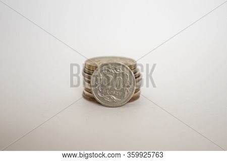 Polish Coin Twenty Grosz. A Coin On A White Background Stands Vertically Next To Other Coins Piled I