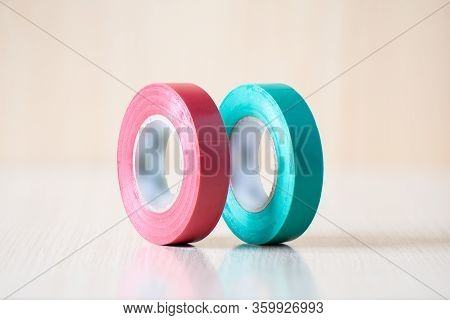 Red And Green Insulating Tapes To Insulate The Twist Of Electrical Wires. Insulating Tapes On A Wood
