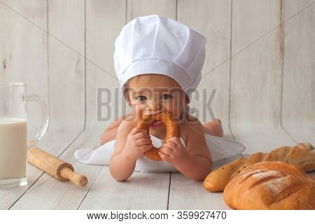 Cute Ten Months Old Baby Boy, In A Suit Of A Cook, Sits On A Light Wooden Background. Chefs Hat On H