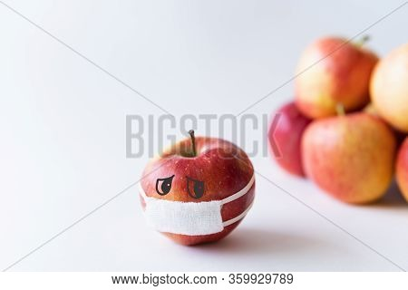 Apple Wearing Medical Mask Isolated From The Crowd. Conceptual Image Of Social Distancing During Cor