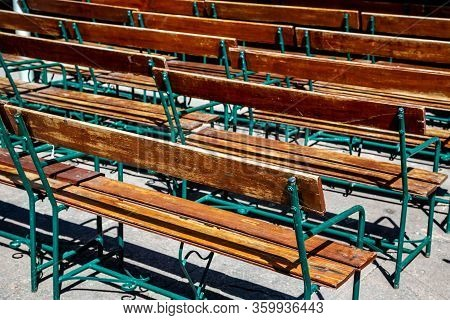 Lot Of Rows Of Empty Brown Wooden Benches Closeup. Rear View