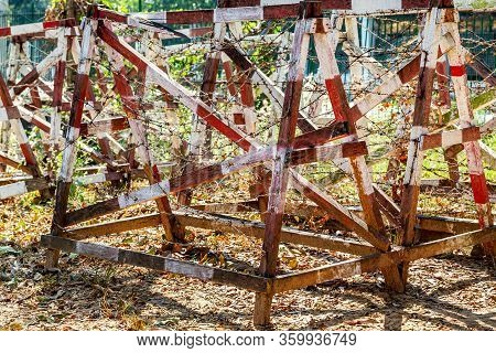 Many Rows Of Wooden Structures In The Form Of Fence With Rusty Barbed Wire To Ensure Safety At The R