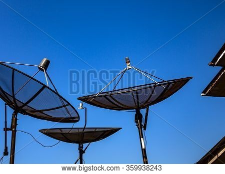 Parabolic Satellite Antenna On Blue Sky Background Closeup