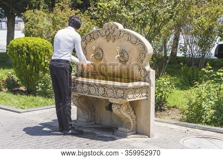 A Man Washes His Hands In The Park At The Water Distribution Point. Corona Virus  Prevention Wash Ha