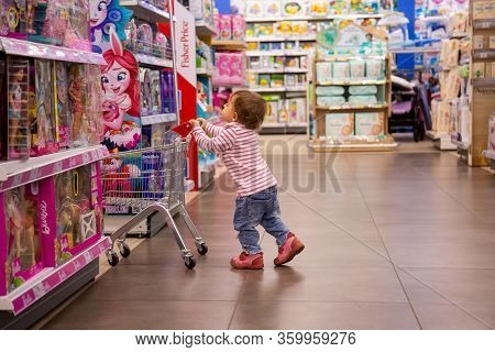 Moscow, Russia - 23 October 2019: Little Cute Baby Girl Rolls A Shopping Trolley In A Toy Store Betw