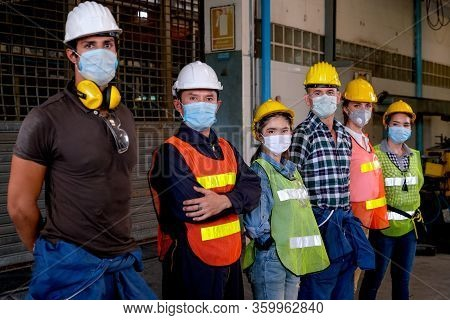 Group Of Workers Or Technician With Mask Stand And Look Right Side Direction And Stay In Factory Are