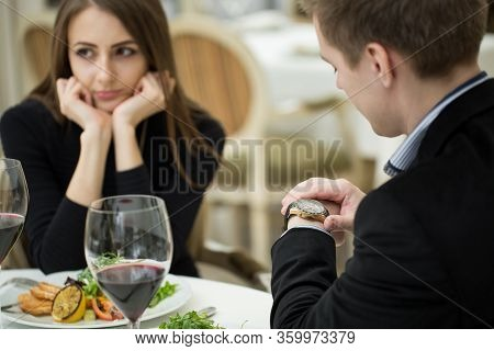 Young Woman Making An Exasperated Expression Gesture On A Bad Date At The Restaurant. Man Looks At H