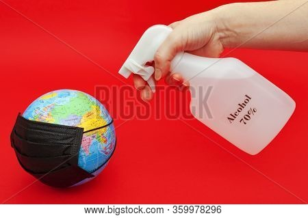 Hand Spraying 70% Alcohol On Terrestrial Globe Model With Black Surgical Mask Isolated On Red Backgr