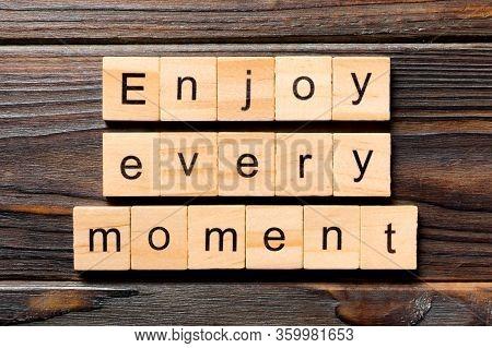 Enjoy Every Moment Word Written On Wood Block. Enjoy Every Moment Text On Wooden Table For Your Desi