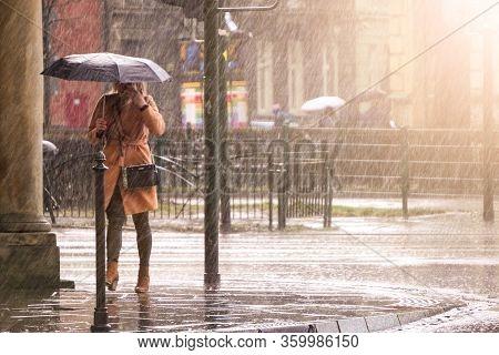 Woman In A Brown Coat Under An Umbrella Crosses A Busy Street In Heavy Rain. Heavy Precipitation In