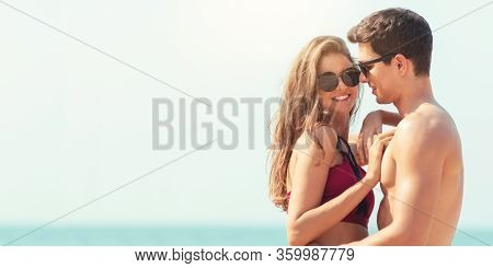 Portrait Of Romantic Young Couple Wear Sun Glasses Embracing Together At The Beach. Happy Smiling Ha