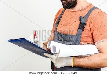 Worker Taking Notes. House Renovation, Service. Experts Use Drawings And Papers For Taking Notes.