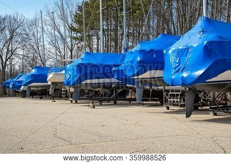Row Of Boats Covered With Blue Shrink Wrap In Outdoor Storage Lot
