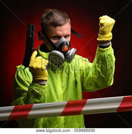 Man In Respirator Ang Gloves With A Gun