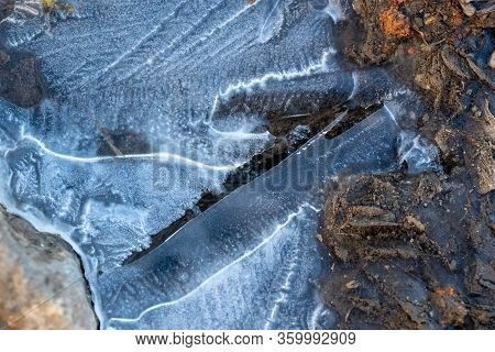 Frozen Puddle. Texture, Thin Ice Surface. The First Thin Crust Of Ice On A Puddle Is Transparent And