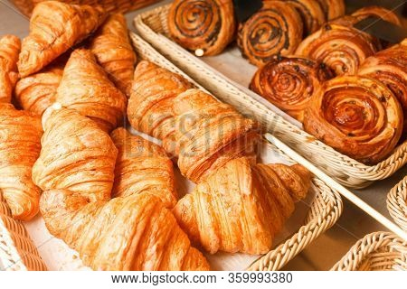 Delicious Freshly Baked Pastries In A Pastry Shop. Many Buns And Croissants On A Shelf Of A Baking S