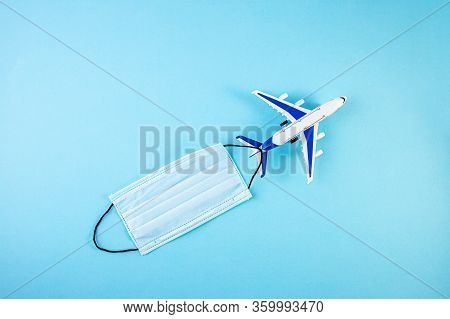 Model Airplane With Protective Medical Mask. Pandemic Covid-19 Coronavirus Quarantine Concept. Perso