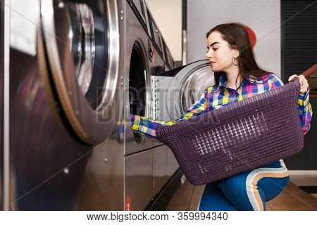 Girl Loads Laundry Into A Washing Machine. Woman In Public Laundry