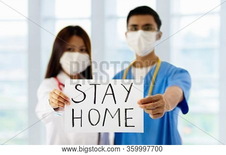 Asian Doctor Or Nurse With Stay Home Sign. Medical Specialist With Stethoscope And Face Mask During