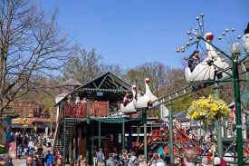 Copenhagen, Denmark - April 21, 2019: Amusement Park Ride And Crowd Of People At Bakken, The Oldest