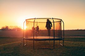 Trampoline On A Lawn In The Sunset With Two Kids And A Young Woman Juping And Playing