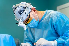 Surgeon Performing Cosmetic Surgery In Hospital Operating Room. Surgeon In Mask Wearing Surgical Lig