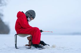 A Boy In Red Overalls On Winter Fishing On The Lake. Sits In An Armchair Near The Hole. In The Hands