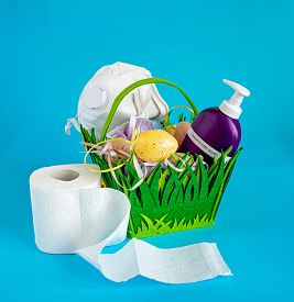Easter basket with a respirator, toilet paper, a sanitizer and Easter eggs. Concept associated with the coronavirus pandemic COVID-19