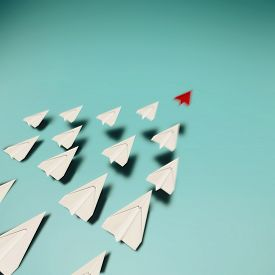 Paper Airplanes Taking Off A Blue Background . Start Up Concept . Red Paper Plane Leader . This Is A