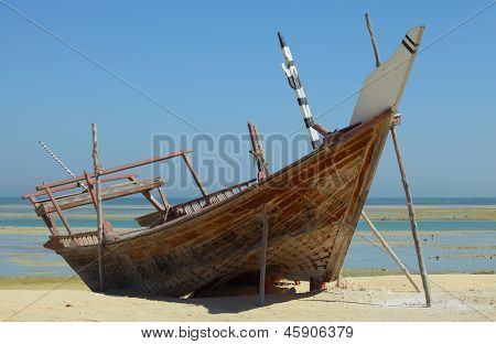 A beached dhow at Wakrah, south of Doha, Qatar. The vessel seems to have been abandoned long ago and is little more than a wreck now