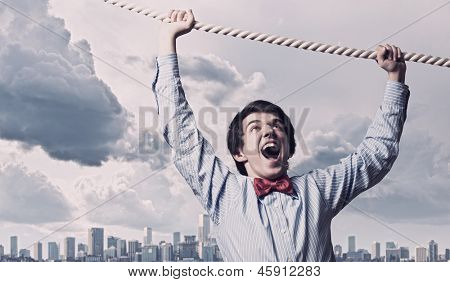 Image of businessman hanging on rope against city background