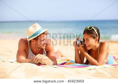 Beach fun couple travel. Woman taking photo picture of man smiling happy with retro vintage camera, Cool trendy modern hipster interracial couple on summer holidays vacation on tropical beach.