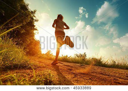 Señora joven corriendo en un camino rural durante la puesta del sol