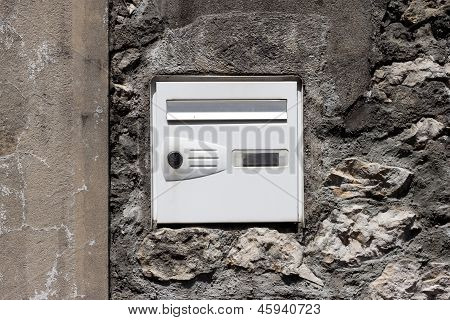 The postal drop box on the stone mason wall.