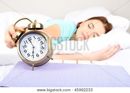 Beautiful young woman sleeping on bed with alarm clock in bedroom