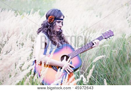 Hippie Girl With The Guitar Walking On A Meadow