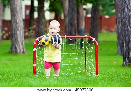 Small Caucasian Boy Plays Football In Park
