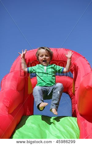 3 year old boy jumping down the slide on an inflatable bouncy castle