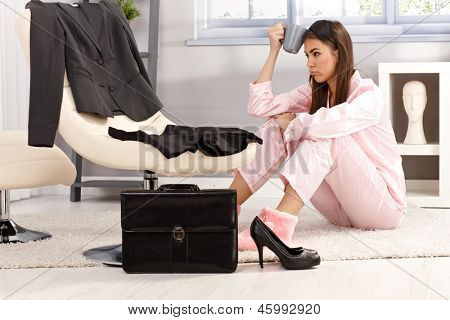 Tired woman getting ready for business work, sitting in pyjama on living room floor, holding coffee mug, annoyed.