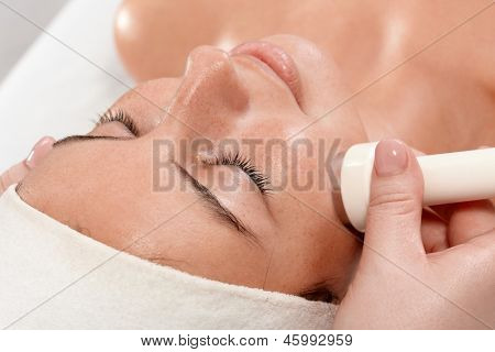 Closeup portrait of young woman receiving facial beauty treatment, laying eyes closed. poster